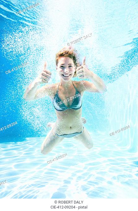Woman giving thumbs up underwater in swimming pool
