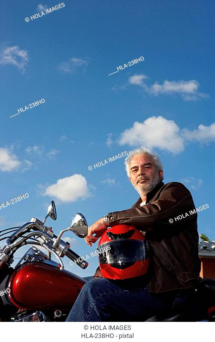 Portrait of a mature man sitting on a motorcycle