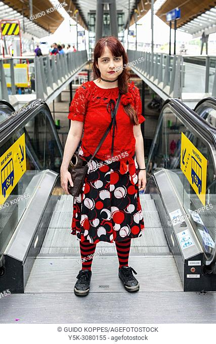 Amsterdam, Netherlands. Streetportrait of a young, redhaired woman riding an escalator from a railway station's platform