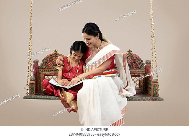 South Indian woman teaching her daughter
