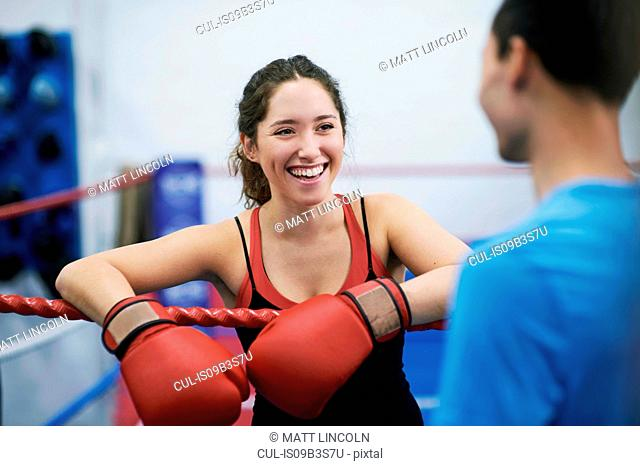 Young female boxer leaning on boxing ring ropes chatting