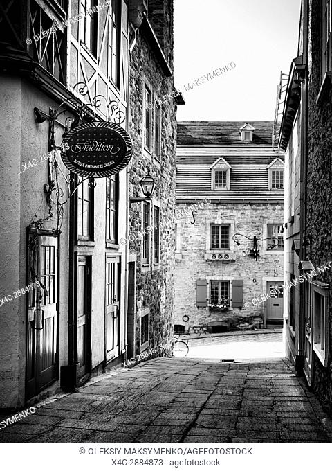 Tradition boutique store sign in a small historic street Rue Pains Benits, historic French architecture of the Old Quebec City. Black and white