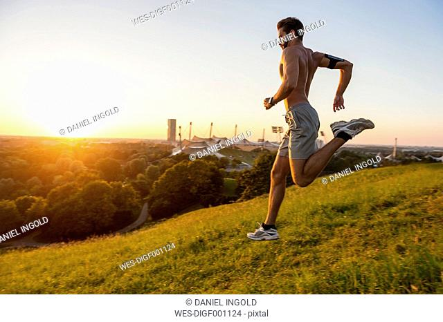 Barechested man running on meadow in park at sunset