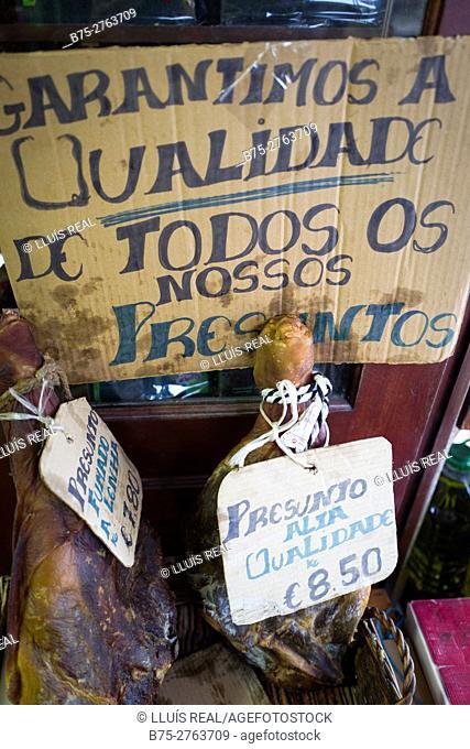 "Cured hams in grocery. Handwritten sign reading ""Garantimos a Qualidad de todos os nossos Presuntos"" (We guarantee the Quality of all our Hams), Ponte de Lima"