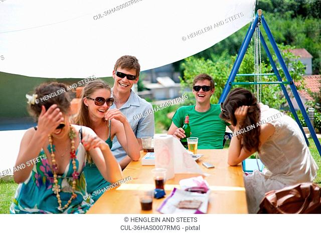 Friends laughing at table outdoors