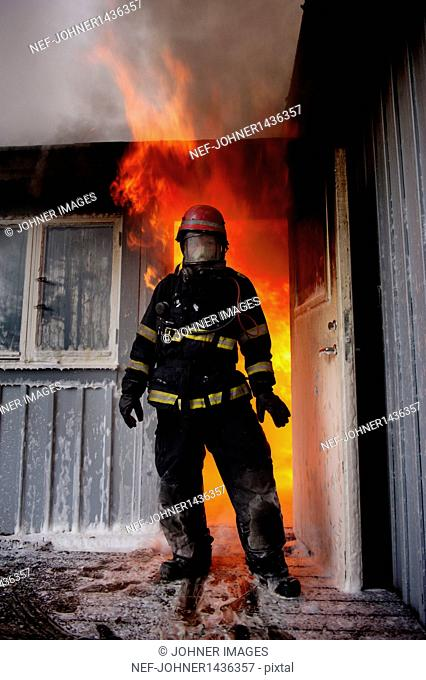 Fire fighter in front burning house