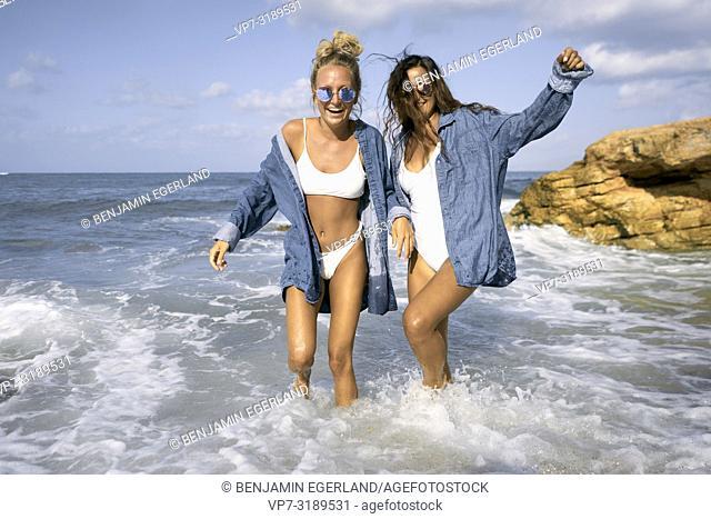 Two women in sea water at beach, Chersonissos, Crete, Greece