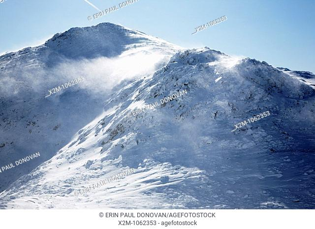 Strong winds cause snow to blow off the summit of Mount John Quincy Adams in the Presidential Range during the winter months in the White Mountains