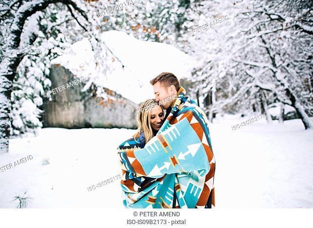 Couple in snow-covered forest wrapped in blanket