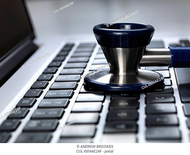 Stethoscope sitting on laptop illustrating online healthcare and doctor's desk