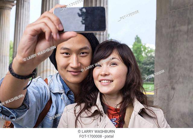 Smiling man taking selfie with young female friend