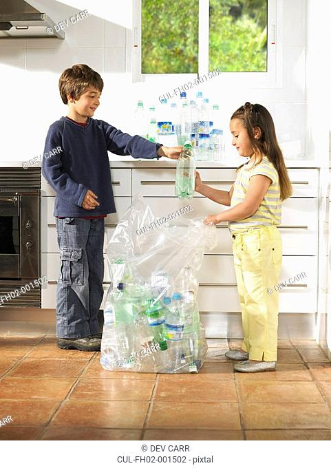 Boy 6-8 and girl 4-6 recycling bottles in kitchen