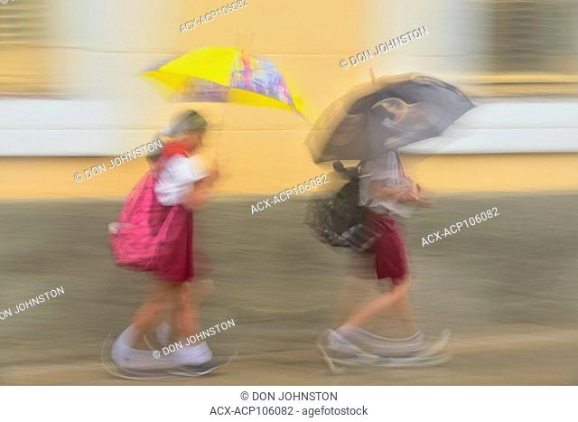 Street photography in central Havana- Schoolgirls with umbrella on a rainy day