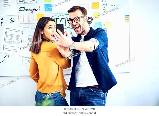 Excited colleagues looking at smartphone in office