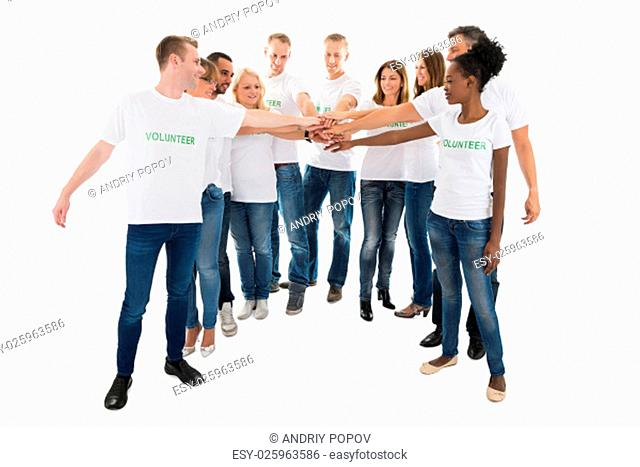 Full length of multiethnic volunteers stacking hands while standing against white background