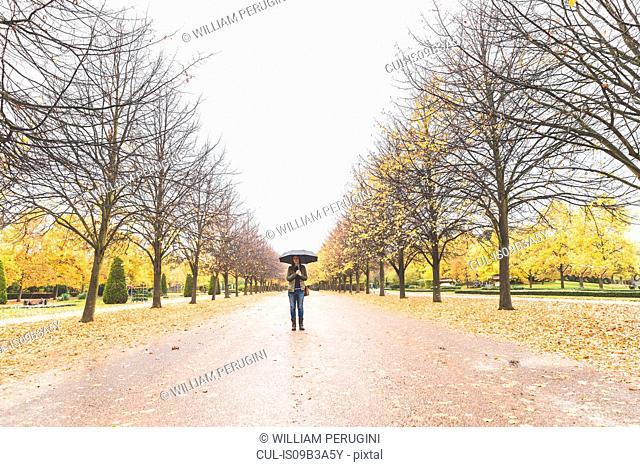Young woman walking through park, carrying umbrella