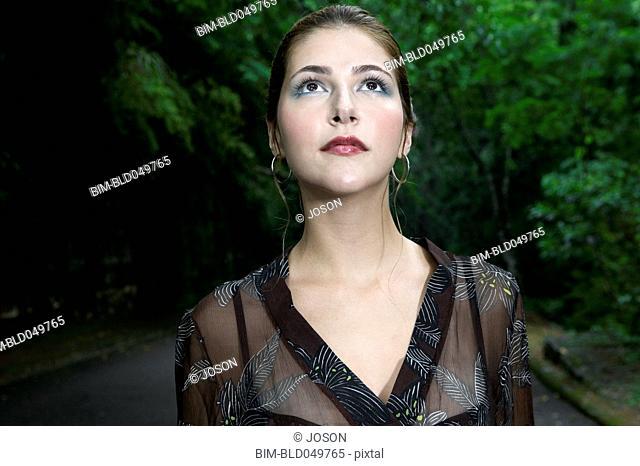 Hispanic woman on road in woods