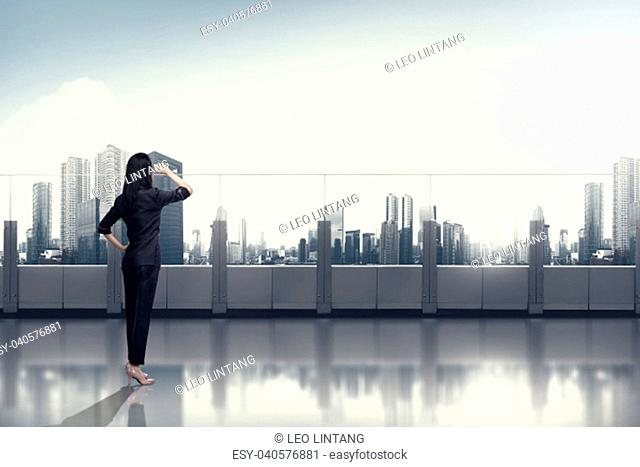 Confidence asian business woman looking at the sky from office balcony