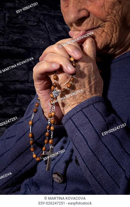 Grandmother praying. Old wrinkled beautiful woman praying with rosary. Faith, spiritualy and religion