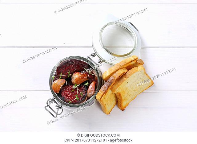 jar of baked beetroot and garlic with toasted bread on white wooden background