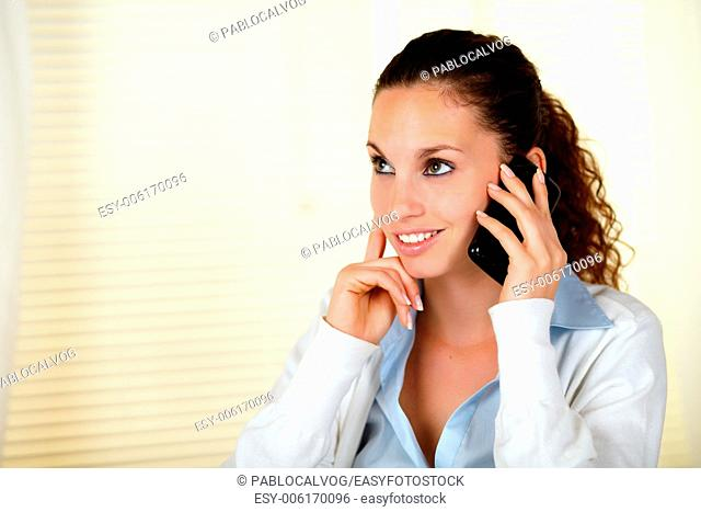 Smiling caucasian woman conversing on cellphone while looking up - copyspace