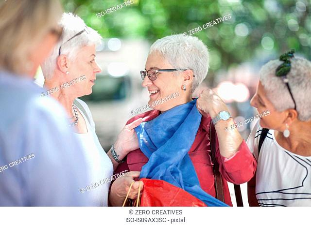 Senior woman and friends chatting in city