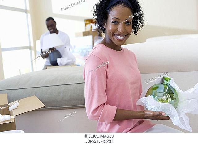Couple moving house, man with lamp, focus on woman unpacking glassware in living room, smiling, portrait