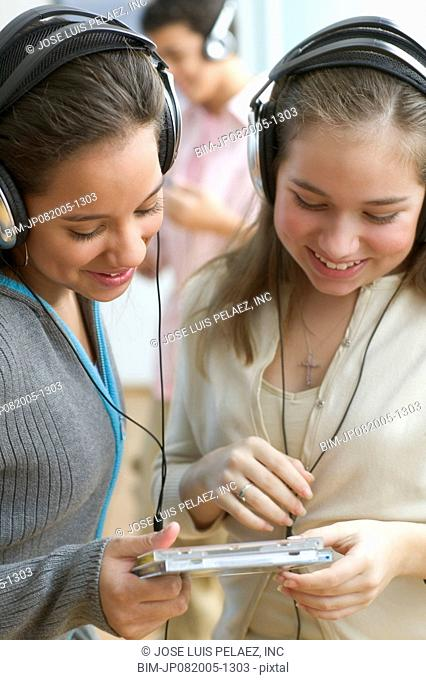 Two teenage girls with headsets listening to music