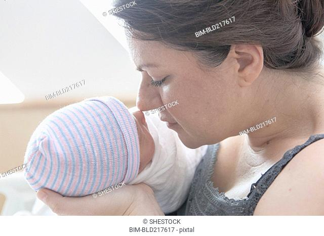 Caucasian mother rubbing noses with newborn daughter