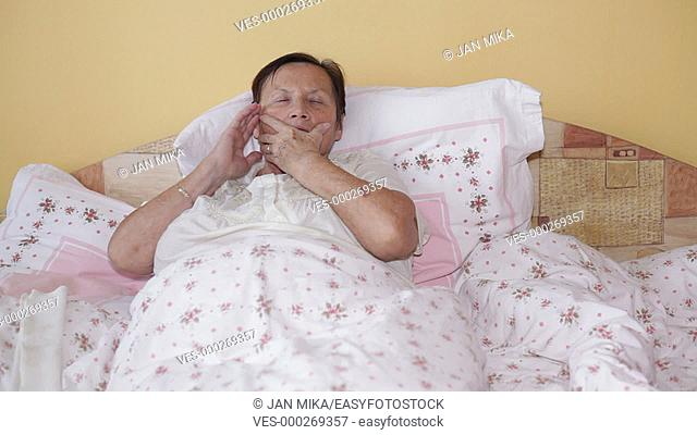 Ill senior woman in bed with painful toothache