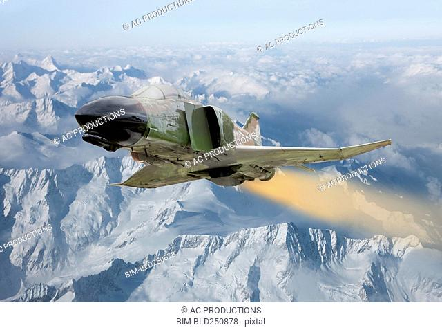 Military jet flying over winter landscape