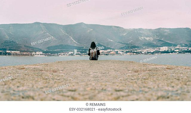 Traveler woman with backpack sitting on pier at bay in front of mountains and town. Space for text in lower part of image