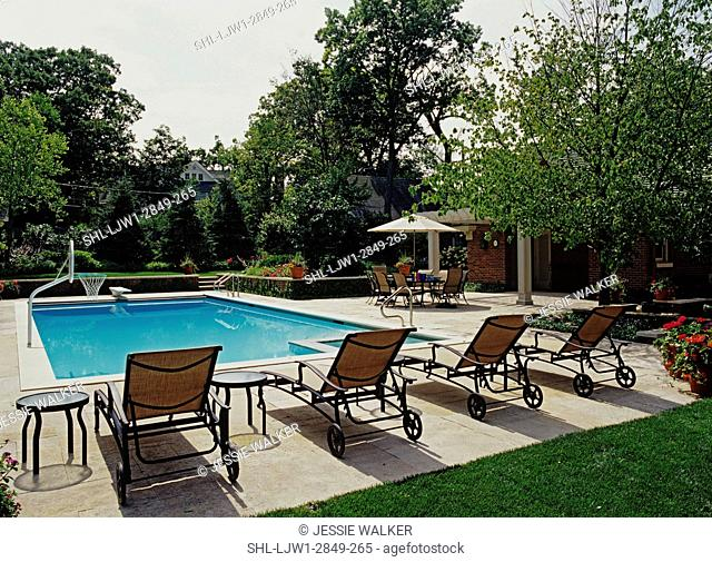 Pool: Overall view of patio and 20' x 46' lap pool, four chaise lounges in foreground, Iowa limestone used throughout, table with umbrella on right