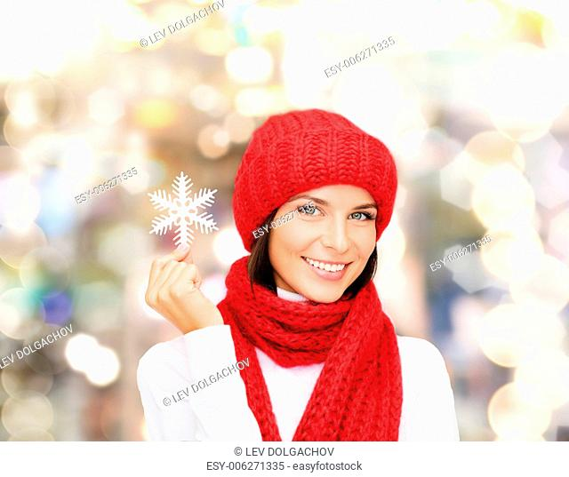 happiness, winter holidays, christmas and people concept - smiling young woman in red hat, scarf and mittens holding snowflake over lights background