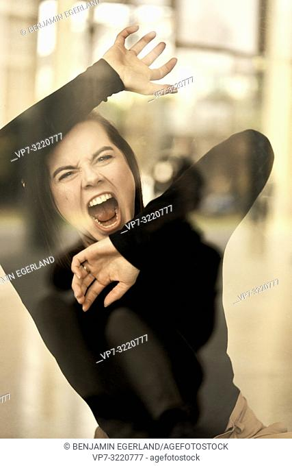 woman screaming behind glass window, furious angry emotion, feeling expelled, mental health, in Munich, Germany