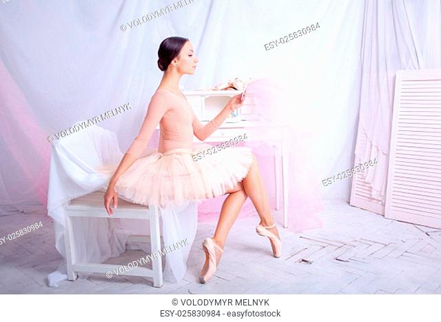Professional ballerina looks in the mirror against the backdrop of pink veil and pointes
