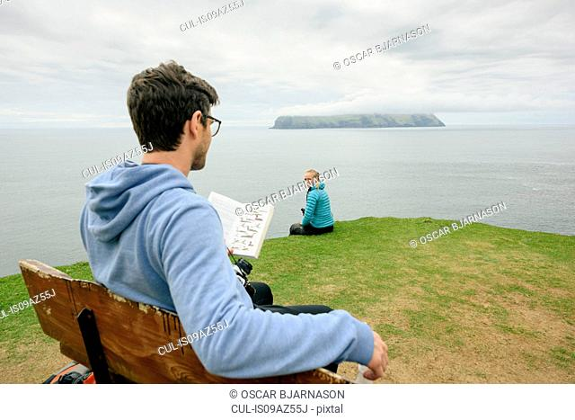 Hikers relaxing and reading book on hill, Gasadalur, Vagar, Faroe Islands