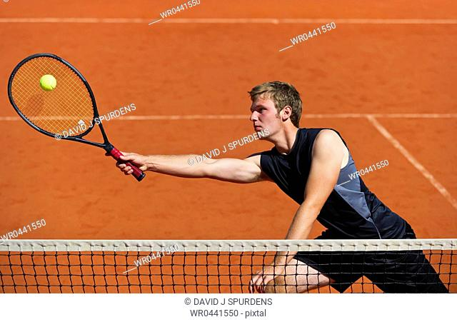 A tennis player at the net stretches to play ball