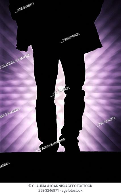 Silhouette of a walking man against a graphic background