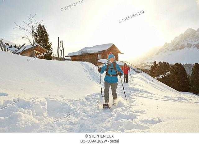 Mid adult couple snowshoeing in deep snow, Dolomites, Eisack Valley, South Tyrol, Italy