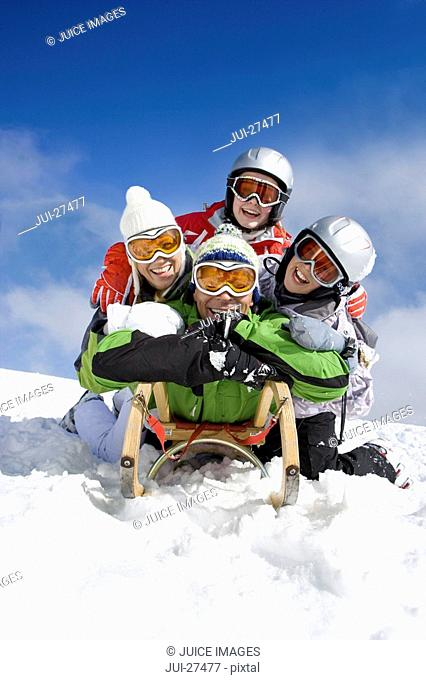 Family laying on sled in snow on mountain top
