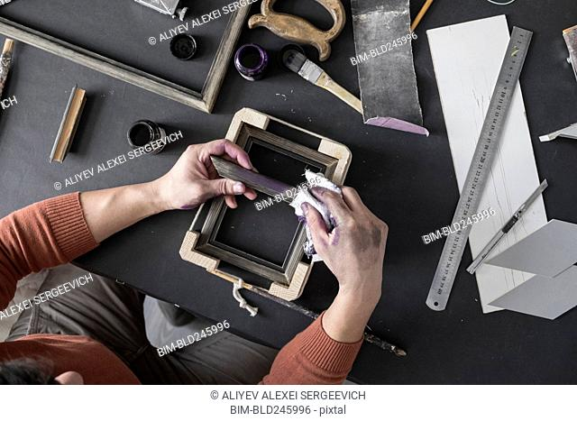 Hands of Caucasian artist staining picture frame