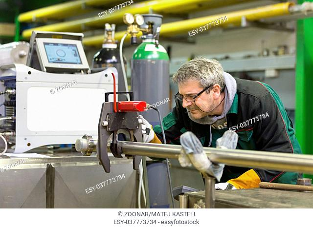 Industrial worker setting orbital welding machine