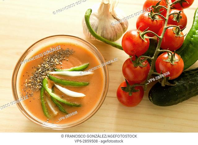 Andalusian gazpacho with ingredients on a wooden background pine