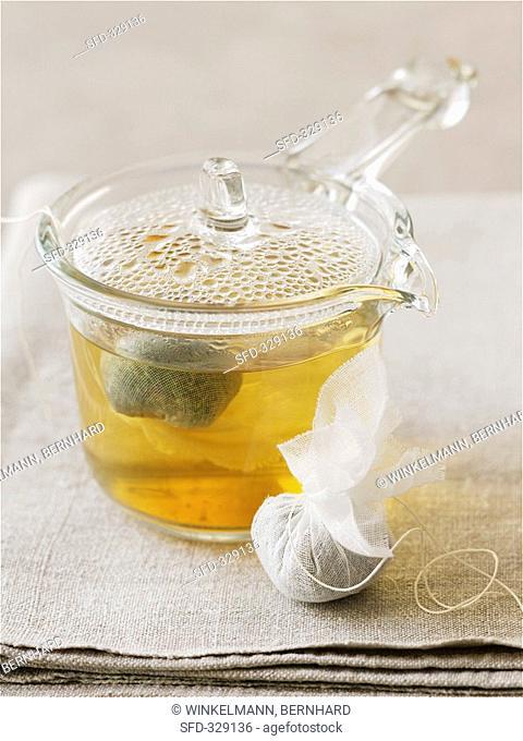 Herbal tea in glass pot and herbs in tea bag