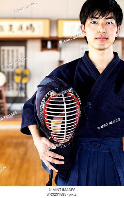 Male Japanese Kendo fighter standing in a gym, holding Kendo mask, looking at camera