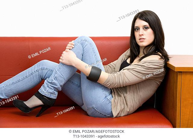Lounging on a Red sofa pretty young woman