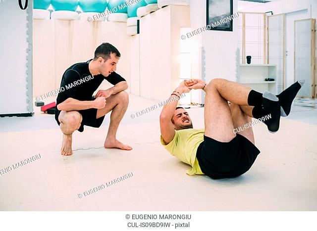 Man doing sit ups with personal trainer