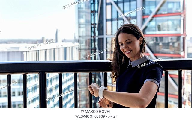 UK, London, smiling woman using smartwatch on a roof terrace