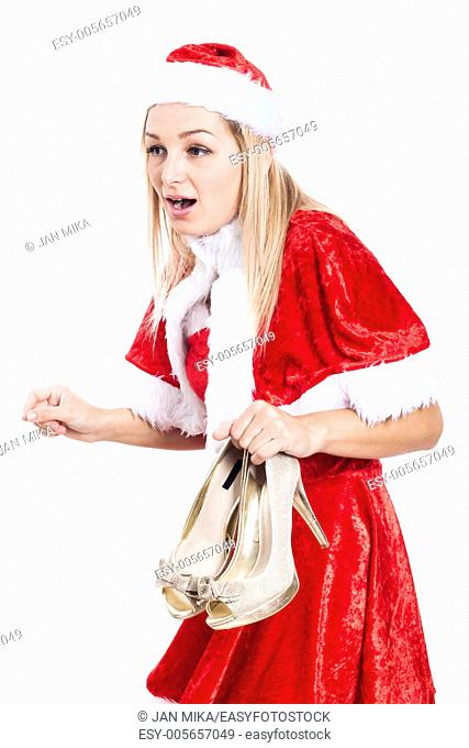 Shocked woman in Christmas costume holding high heel shoes, isolated on white background